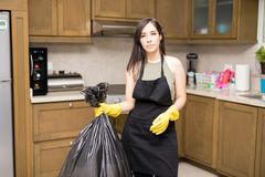 Young maid holding garbage bag in kitchen. Housewife wearing black  apron and yellow protective rubber gloves holding garbage bag Royalty Free Stock Images