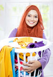 Housewife wearing hijab carrying laundry basket full of dirty cl Stock Photos