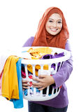 Housewife wearing hijab carrying laundry basket full of dirty cl Royalty Free Stock Images