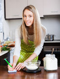 Housewife  weighing floor on kitchen scales Royalty Free Stock Image