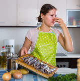 Housewife wincing of fish smell. Housewife in apron cooking fish and wincing of disgusting smell Royalty Free Stock Photography