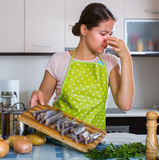 Housewife wincing of fish smell. Housewife in apron wincing of disgusting smell of fish at kitchen Stock Photo