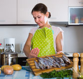 Housewife wincing of fish smell. Young housewife in apron cooking fish and wincing of disgusting smell Stock Photo