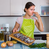 Housewife wincing of fish smell. Young housewife cooking fish and wincing of disgusting smell Stock Photography