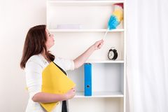 Housewife wiping dust off the shelves Stock Photography