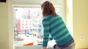Housewife woman clean window with rag. Flat house living district view from window stock video