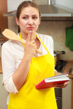 Housewife woman with cookbook in kitchen. Royalty Free Stock Photos