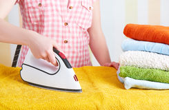 Housewife  woman with iron engaged in domestic work Stock Photography