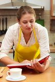 Housewife woman reading cookbook in kitchen. Royalty Free Stock Images