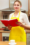 Housewife woman reading cookbook in kitchen. Stock Image