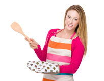 Housewife with wooden spatula and warmth insulation gloves Royalty Free Stock Photos