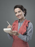 Housewife writing down recipe ingredients. Smiling vintage housewife writing down a recipe ingredients on a notepad Royalty Free Stock Photo
