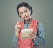 Housewife writing down a shopping list Royalty Free Stock Image