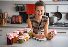 Housewife writing in notepad in kitchen Stock Images