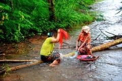 Housewifes rurales que lavan la ropa de la manera tradicional en r bajo Imagen de archivo