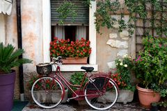 Housewives bike. Bicycle with a shopping basket parked under the window of an old house in Lazise town at Garda Lake Stock Photo