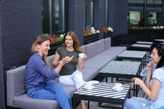 Housewives meeting at cafe and drinking coffee. Concept of free time and gossips Royalty Free Stock Photos