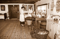 Housewives pickling cabbage in ancient times (sepia). Kitchen in farmhouse, ethnographic museum in Poland. Two women slicing and shredding white cabbage Royalty Free Stock Photo