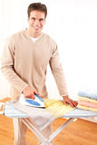 Housework. Happy young handsome man ironing clothes. Housework royalty free stock image