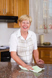Housework. A happy european senior woman doing housework, she is cleaning her kitchen counter royalty free stock images