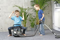 Housework. Two brothers have fun with cleaning carper - housework stock photography
