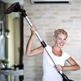 Housework. Chores around the house. Young  housewife with a vacuum cleaner Royalty Free Stock Images