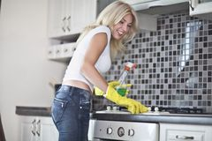 Housework. Chores around the house. Young  housewife cleans the kitchen Stock Image
