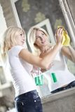 Housework. Chores around the house. Young  housewife cleans the mirror Royalty Free Stock Photos