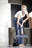 Housework. Chores around the house. Young  housewife with a vacuum cleaner Stock Photo