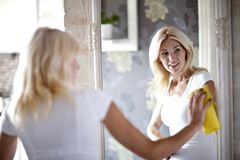 Housework. Chores around the house. Young  housewife cleans the mirror Royalty Free Stock Image
