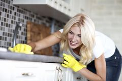 Housework. Chores around the house. Young  housewife cleans the kitchen Stock Photo