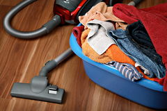 Housework concept. Vacuum cleaner and laundry on wooden floor Stock Photos