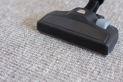Close up of modern vacuum cleaner over carpet Royalty Free Stock Photography