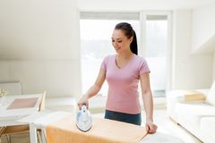 Woman or housewife ironing towel by iron at home Stock Photos