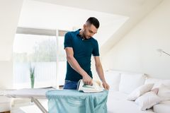 Man ironing shirt by iron at home Stock Photo