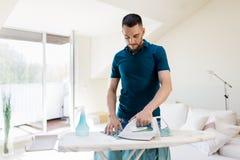 Man ironing shirt by iron at home Royalty Free Stock Photos