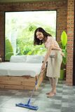 Housework and housekeeping concept. Woman cleaning floor with mo stock photo