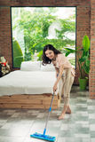 Housework and housekeeping concept. Woman cleaning floor with mo. P indoors Stock Photography