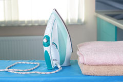 Housework, ironing iron colorful towels on the ironing board. Royalty Free Stock Photography