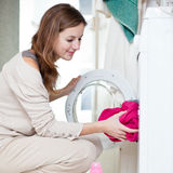 Housework: mulher nova que faz a lavanderia imagem de stock royalty free