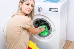 Housework: mulher nova que faz a lavanderia Imagem de Stock