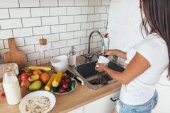 housework Pratos de lavagem da jovem mulher na cozinha foto de stock royalty free