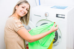 Housework: young woman doing laundry. Putting colorful garments into the washing machine (shallow DOF; color toned image Stock Images