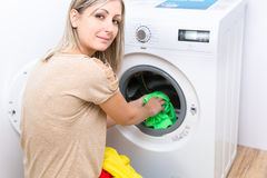 Housework: young woman doing laundry Royalty Free Stock Photography