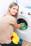 Housework: young woman doing laundry. Putting colorful garments into the washing machine (shallow DOF; color toned image Royalty Free Stock Photos