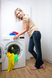 Housework: young woman doing laundry. Putting colorful garments into the washing machine (shallow DOF; color toned image Royalty Free Stock Images