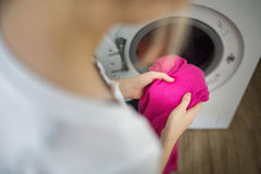 Housework: young woman doing laundry Stock Image