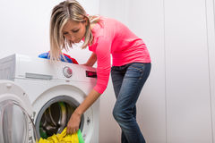 Housework: young woman doing laundry Stock Images