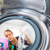 Housework: young woman doing laundry Royalty Free Stock Photo