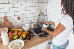 Housework. Young woman washing dishes in kitchen. Housework. Young woman washing dishes in kitchen Royalty Free Stock Photo